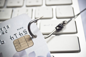 hand holding a credit card with a fish hook - phishing